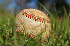 Alter Baseball im Gras Stockbild