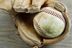 Alter Baseball und Handschuh auf verblaßtem Holz stockfotografie