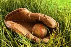 Alter Baseballhandschuh mit Kugel im Gras lizenzfreies stockfoto