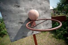 Alter Basketball und Korb auf verwitterter hölzerner Fassade stockbilder