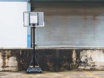 Alter Basketballpfosten nahe der Fensterladentür Stockfoto