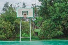 Alter Basketballplatz im Freien im Park mit grünem natürlichem im Hintergrund stockbild