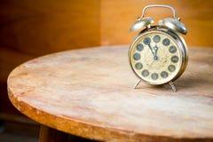 Alter benutzter Wecker auf gerundeter Tabelle Veraltete Technologie aber großer Entwurf - fünf bis zwölf stockbild