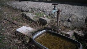 Alter Bratenfett-Hahn Wasserkasten mit altem Hahnbratenfett in der Landschaft stock video