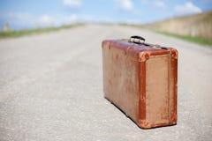 Alter brauner Koffer steht auf einer Wüstenstraße stockfoto