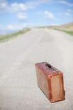 Alter brauner Koffer steht auf einer Wüstenstraße lizenzfreies stockbild