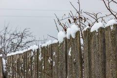 Alter Bretterzaun mit Schnee Stockfoto