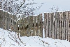 Alter Bretterzaun mit Schnee Stockfotos