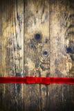 Alter Bretthintergrund mit rotem festlichem Band. Lizenzfreie Stockfotos