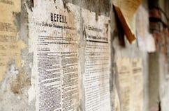 Alter Deutscher schädigte Plakatzeitungsnachrichten auf einer Wand Lizenzfreie Stockfotografie