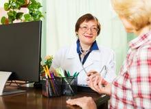 Alter Doktor, der gute Nachrichten für einen Patienten hat Stockbild