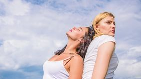 Alter ego concept. Blonde and brunette back to back. Concentrated and relaxed. Friend you trust. Friendship and trust. Female friendship. Women lean each other stock photo