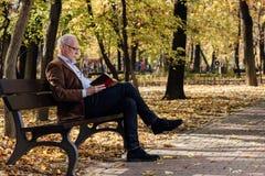 Alter eleganter Mann, der draußen ein Buch liest Lizenzfreies Stockbild