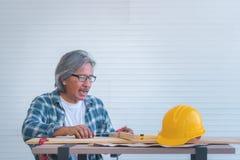 Alter Erbauer mit Werkzeugen und Papierplan auf Funktionstabelle lizenzfreie stockbilder