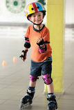Alter Fünfjahresjunge mit seinem Daumen, der oben zeigt, dass er Rollschuhlaufen mag Ausgerüsteter Junge, der einen Sturzhelm trä Lizenzfreies Stockfoto
