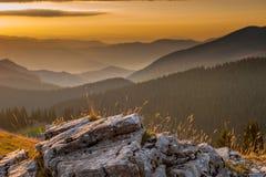 Alter Felsen mit Sonnenaufgang über Gebirgszügen Lizenzfreie Stockbilder