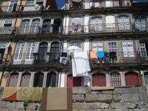 Alter Fensterbalkon der typischen bunten portugiesischen Architektur und moderne gesessene Teller und Wäschereitrockner lizenzfreies stockfoto