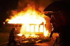 Alter Feuerwehrmann betrachtet ein großes Hausfeuer. Stockbilder