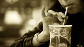Alter Filmeffekt: junges Mädchen trinkt kaltes Getränk mit einem Stroh stock video footage