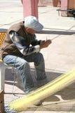 Alter Fischer, der seine Netze an Tasucu-Hafen ausbessert stockbild