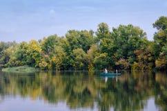 Alter Fischer im Boot. Ruhiger Fluss, früher Herbst Stockbilder