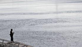 Alter Fischer wirft ein Angelrutenspinnen der alte Mann ist Fisch Stockfotografie