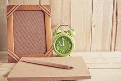 Alter Fotorahmen, -notizbuch, -uhr und -bleistift auf Holztisch Stockfotos