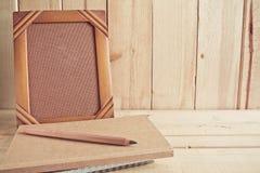 Alter Fotorahmen, -notizbuch und -bleistift auf Holztisch Lizenzfreie Stockfotografie