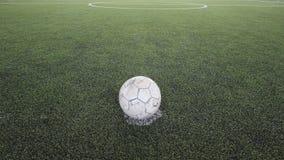 Alter Fußball auf dem gefälschten Gras Lizenzfreie Stockfotos