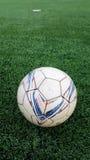 Alter Fußball auf dem grünen künstlichen Rasen Lizenzfreie Stockfotografie