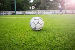 Alter Fußball auf künstlichem Rasenfußballplatzgrün Lizenzfreie Stockfotografie