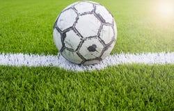 Alter Fußball auf künstlichem Rasenfußballplatzgrün-Weißgitter Lizenzfreies Stockfoto