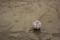 Alter Fußball, der auf einem Schlammboden bleibt Lizenzfreies Stockfoto