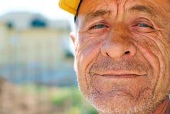 Alter geknitterter Mann mit gelber Schutzkappe Lizenzfreie Stockfotografie