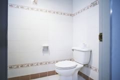 Alter, generischer Toilettentoilettenraum der Wohnung oder Spültoilette des kleinen Hotels mit einfachem Fliesenmuster stockbilder