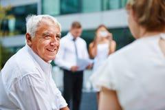 Alter Geschäftsmann, der mit Geschäftsteam spricht stockfotografie