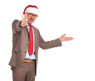 Alter Geschäftsmann, der Weihnachtsmann-Hut o.k. sich darstellt und macht trägt Lizenzfreie Stockfotos