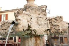 Alter geschnitzter Brunnen im Marktplatz der kleinen französischen Stadt Lizenzfreie Stockfotos