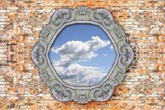 Alter geschnitzter Steinrahmen mit dem Himmel in der Mitte auf Backsteinmauer Stockbild