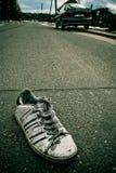 Alter getragener einzelner Stiefel auf der Straße Stockfotos