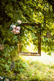 Alter goldener Rahmen, verziert mit den Blumen, hängend an einem Niederlassungsgrünhintergrund Blumendekor für Heiratsfotoaufnahm Stockfotografie