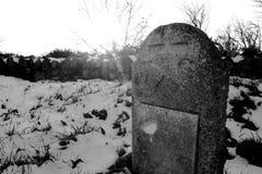 Alter Grabstein im schneebedeckten Kirchhof Stockfotografie