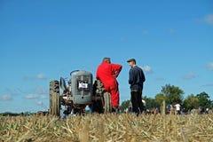 Alter grauer Ferguson-Traktor und roter entsprochener Fahrer stockbilder
