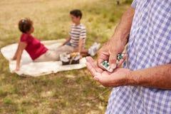 Alter Großvater mit der Familie, die Medizin-Pille für Herz einnimmt Stockfotografie