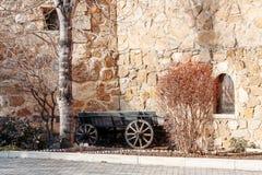 Alter hölzerner Wagen gegen Hintergrund einer merkwürdigen Steinwand der Festung lizenzfreie stockfotos