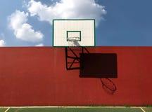 Alter hölzerner Basketballkorb auf einer orange Zementwand mit klarem blauem Himmel und Wolken lizenzfreie stockbilder
