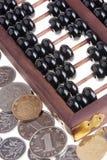 Alter hölzerner chinesischer Abakus und chinesische Münzen Stockbilder