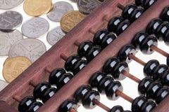 Alter hölzerner chinesischer Abakus und chinesische Münzen Stockfoto