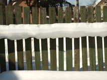 Alter hölzerner Dorfzaun bedeckt mit Schnee Verschneiter Winter in Stockfoto