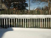 Alter hölzerner Dorfzaun bedeckt mit Schnee Verschneiter Winter in Lizenzfreie Stockbilder